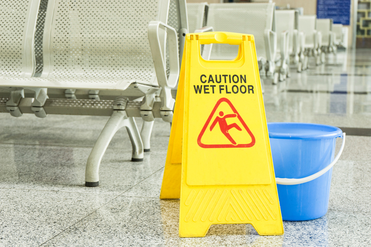 wet floor sign in front of a blue bucket