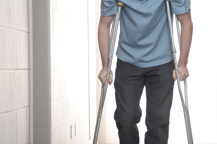 young man with blue shirt walking with crutches