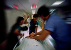 doctors rushing a man on a gurney down the hall